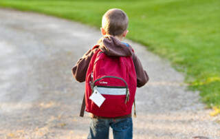 Young boy walking to school with backpack