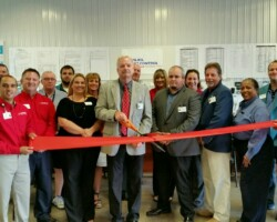 Group of Wil-Kil employees cutting ribbon.