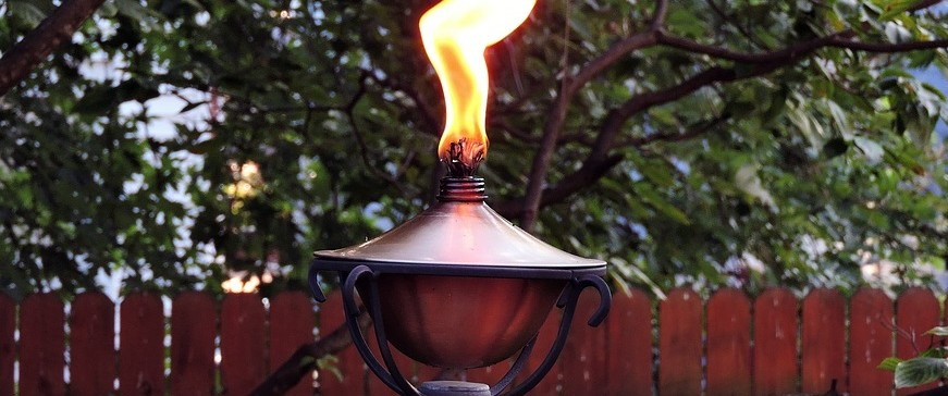 Close up of lit tiki torch in backyard.