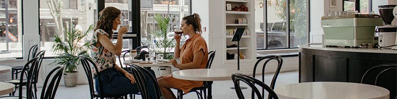 Two women drinking coffee inside restaurant